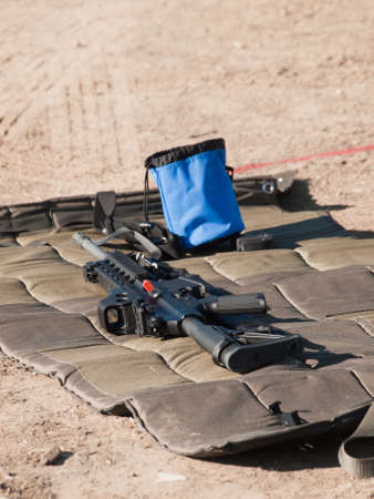 Rifle on the shooting mat with safety on. Stock Photo