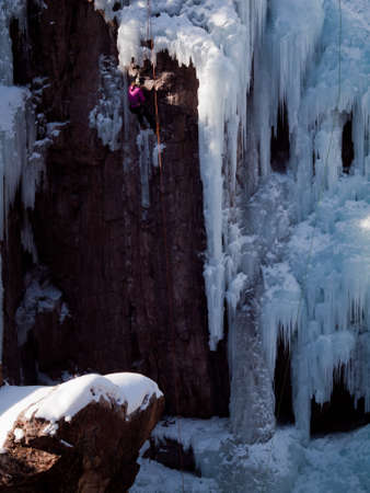 january 1: Alpinist ascenting a frozen waterfall in Ice park, Ouray.
