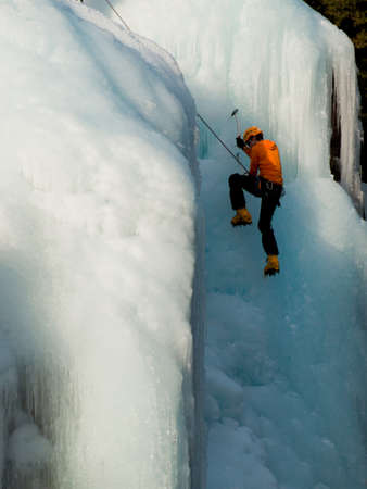 Alpinist ascenting a frozen waterfall in Ice park, Ouray. photo