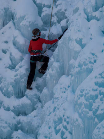 Alpinist ascenting a frozen waterfall in Ice park, Ouray.