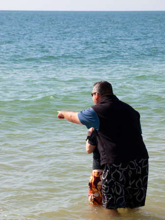 Father and son standing in water on Mexico Beach, Florida. photo