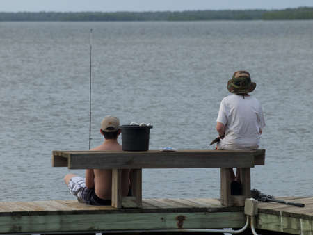 Two brothers fishing from the pier at the Chokoloskee Island. photo