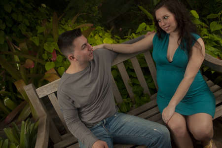 Pregnant woman and husband spending time in the garden. photo