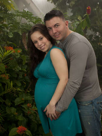 Pregnant woman and husband spending time in the garden. Foto de archivo