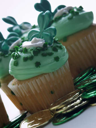 Decorated cupcakes in a festive St. Patricks day setting with shamrocks. photo