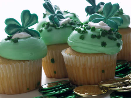 patrics: Decorated cupcakes in a festive St. Patricks day setting with shamrocks.