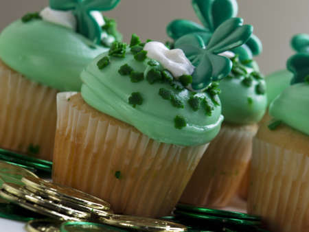 Decorated cupcakes in a festive St. Patrick's day setting with shamrocks. photo