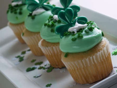 Decorated cupcakes in a festive St. Patricks day setting with shamrocks.