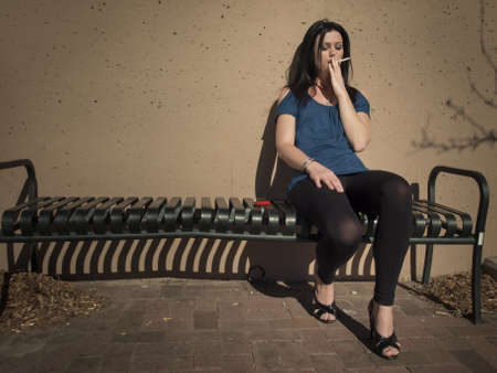 Real young woman smokes on the bench. photo