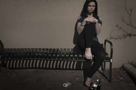 peer pressure: Real young woman smokes on the bench.