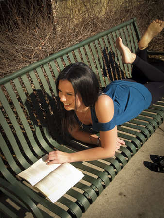 denver parks: Young woman reading book in the park.