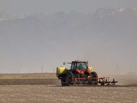 Spring plowing in sand storm near Alamosa, Colorado.