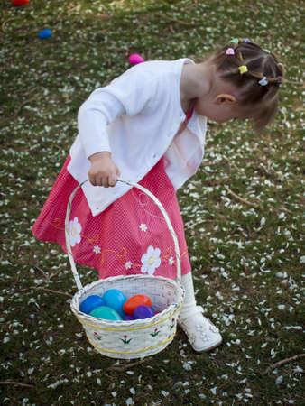 easter egg hunt: Little toddler girl on Easter egg hunt in urban park.