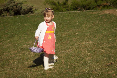 Little toddler girl on Easter egg hunt in urban park. photo