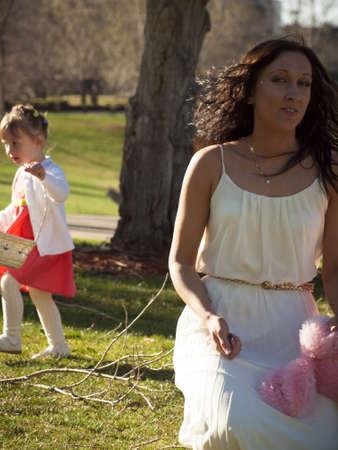 Little toddler girl on Easter egg hunt in urban park. photo
