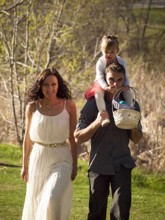 shoulder carrying: Little toddler girl on Easter egg hunt in urban park.