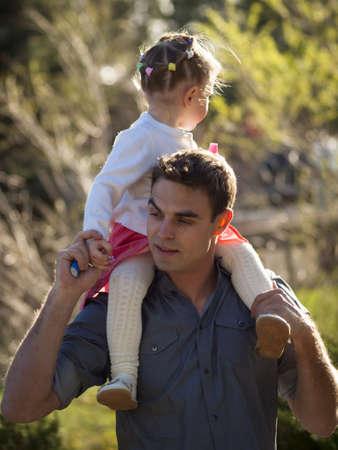 shoulder ride: Familia joven con el ni�o ni�a en parque urbano.