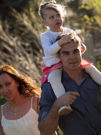 shoulder ride: Familia joven con ni�o ni�a en el parque urbano.