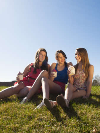 Teenage girls eating frozen soft serve yogurt. Stock Photo - 13155091