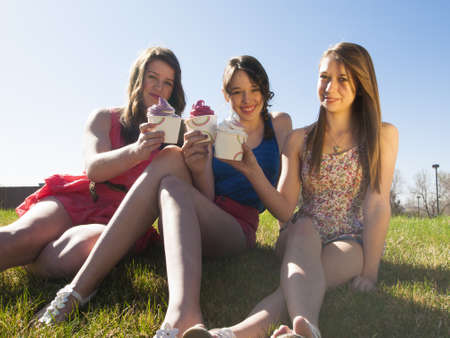 frozen fruit: Teenage girls eating frozen soft serve yogurt.