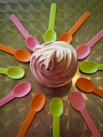 frozen fruit: Spoons and cup with frozen soft serve yogurt. Stock Photo