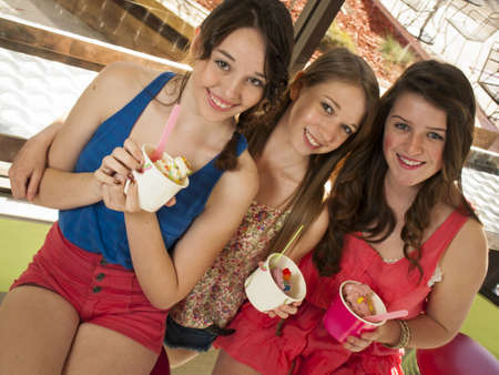 Teenage girls eating frozen soft serve yogurt.