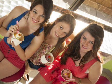 Teenage girls eating frozen soft serve yogurt. Stock Photo - 13155330
