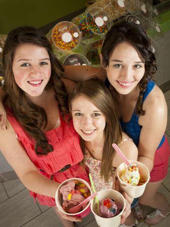 Teenage girls eating frozen soft serve yogurt. photo