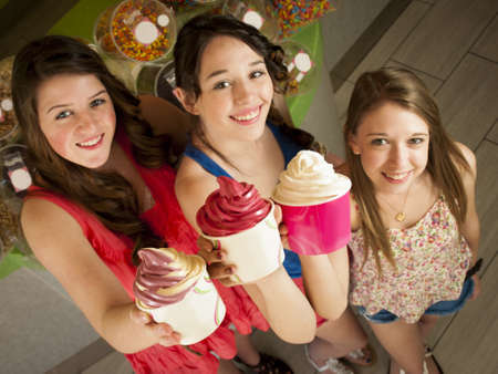 frozen fruit: Teenage girls eating frozen soft serve yogurt.