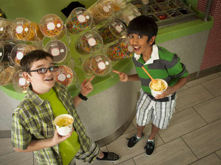 Boys eating frozen soft serve yogurt. photo