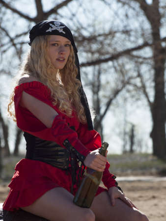 Beautiful young female pirate in red dress. photo