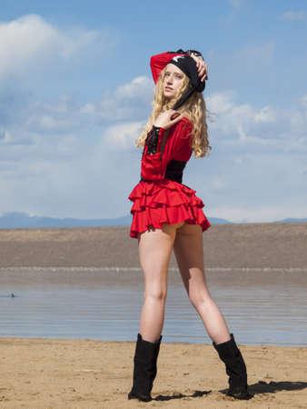 Mooie jonge vrouwelijke piraat in rode jurk.