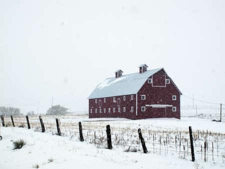 Red barn in snow storm in Colorado.