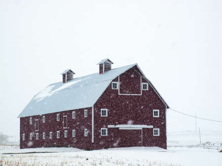 Red barn in snow storm in Colorado.