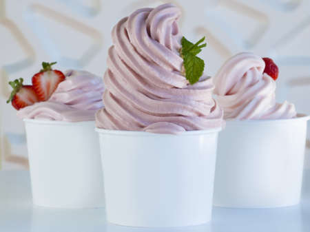 red swirls: Cup of strawberry frozen yogurt or soft serve ice cream with fresh fruit.