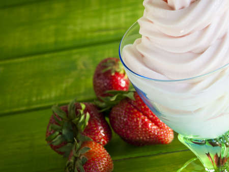 Cup of strawberry frozen yogurt or soft serve ice cream with fresh fruit. photo