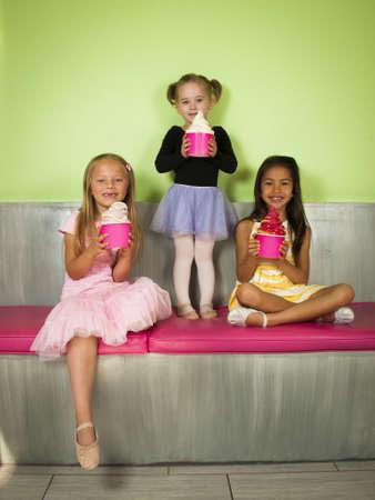 comiendo helado: Bailarinas jóvenes se divierten con yogur congelado suave servido.
