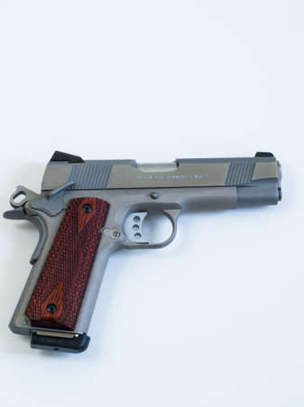 Colt 1911 Commander is a single-action, semi-automatic, magazine-fed, and recoil-operated handgun based on the John M. Browning designed M1911. It was the first mass-produced pistol with an aluminium alloy frame and the first Colt pistol to be chambered i Stock Photo - 13669587