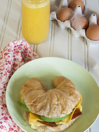 Croissant breakfast sandwich with orange juice served for breakfast. photo