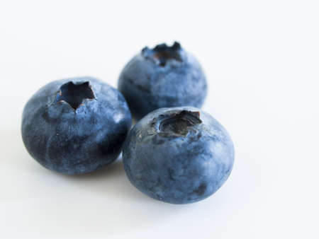 Fresh bluberries from local market on white background. Blueberries contain anthocyanins,  and various phytochemicals, which possibly have a role in reducing risks of some diseases. Imagens