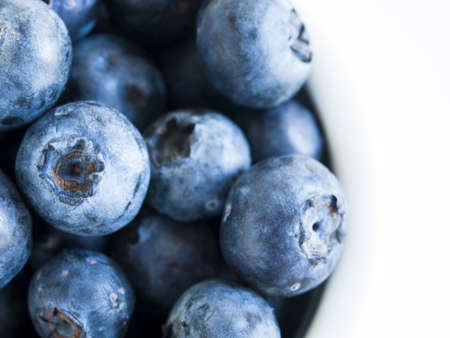 possibly: Fresh bluberries from local market on white background. Blueberries contain anthocyanins,  and various phytochemicals, which possibly have a role in reducing risks of some diseases. Stock Photo