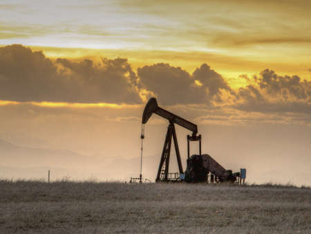 nonrenewable: A pumpjack silhoutte with dramatic sunset.