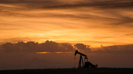A pumpjack silhoutte with dramatic sunset. photo
