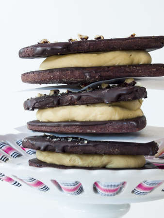 baked treat: Chocolate cookies with peanut butter filling on white background.