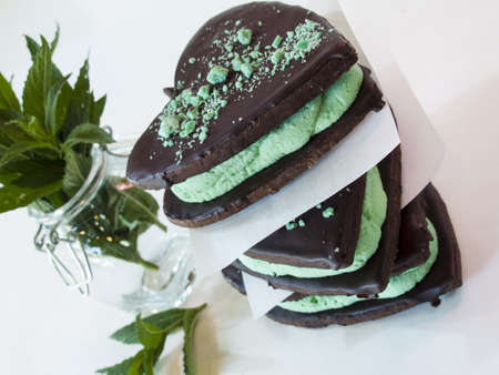 baked treat: Chocolate cookies with mint filling on white background. Stock Photo