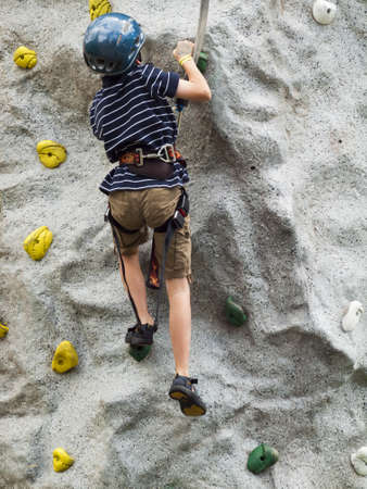 A boy learning how to rock climb.