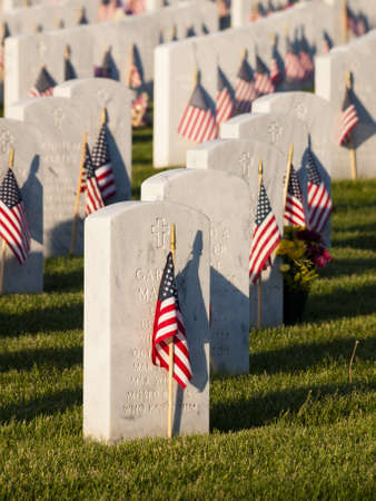 Endless row of white marble gravestones continues above hilltop at the Fort Logan National Cemetery in Denver, Colorado. American flags decorating each grave to mark the Memorial Day. Editorial