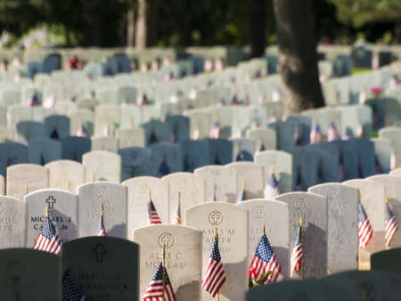 Endless row of white marble gravestones continues above hilltop at the Fort Logan National Cemetery in Denver, Colorado. American flags decorating each grave to mark the Memorial Day.