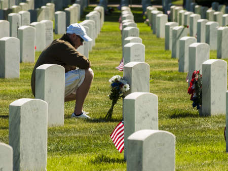 fort logan colorado: Endless row of white marble gravestones continues above hilltop at the Fort Logan National Cemetery in Denver, Colorado. American flags decorating each grave to mark the Memorial Day. Editorial