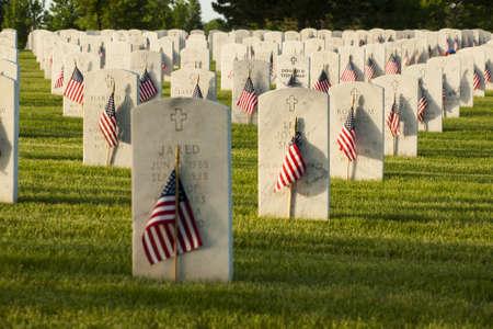 Eindeloze rij van wit marmer grafstenen loopt door boven heuveltop in het Fort Logan National Cemetery in Denver, Colorado. Amerikaanse vlaggen versieren ieder graf aan het Memorial Day te markeren.